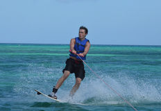 Wakeboarder Landing a Jump After a Doing a 180 in Aruba. Young wakeboarder landing a jump after doing a 180 degree turn Royalty Free Stock Photography