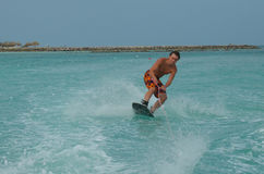 Wakeboarder Leaning into a Turn on a Wakeboard in Aruba. Young guy leaning into a turn on a wakeboard in Aruba Royalty Free Stock Photo