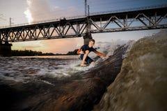 Wakeboarder maschio sorridente che sta sull'un ginocchio sul bordo fotografia stock