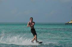 Wakeboarder que crea un espray mientras que monta un Wakeboard Fotografía de archivo
