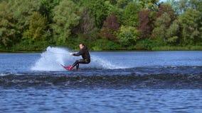 Wakeboarder que faz truques na água Wakeboarder do desportista que salta através da onda filme