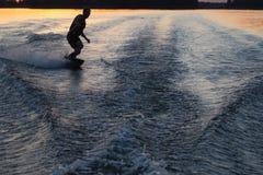 Wakeboarder que faz truques no por do sol Fotografia de Stock Royalty Free