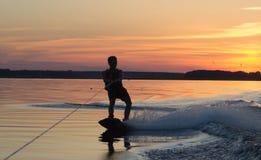 Wakeboarder que hace trucos en puesta del sol Imagen de archivo libre de regalías