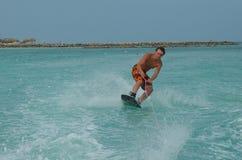 Wakeboarder que se inclina en una vuelta en un Wakeboard en Aruba Foto de archivo libre de regalías
