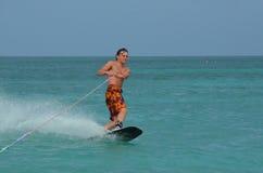 Wakeboarder que talla en un Wakeboard en Aruba Foto de archivo libre de regalías