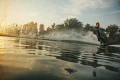 Wakeboarder skiing on lake at sunset Royalty Free Stock Photography