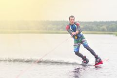 Wakeboarder trains in the lake at sunny day. Space for text stock image