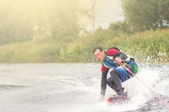 Wakeboarder trains in the lake at sunny day. Space for text stock images