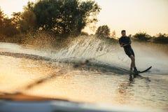 wakeboarding在汽艇后的湖的人 免版税库存照片