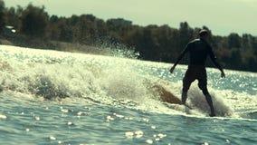 wakeboarding在河和投掷的绳索的波浪的活跃运动员 影视素材
