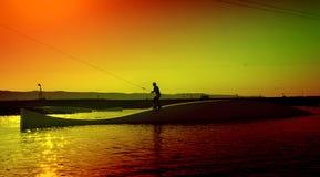 Wakeboarding idrottsman på glidaren i cableparken, solnedgångse Royaltyfria Bilder