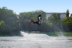 While wakeboarding man jumping over the waves. MOSCOW - JUL 13: While wakeboarding man jumping over the waves on a board on the river in Sokolniki on July 13 stock images