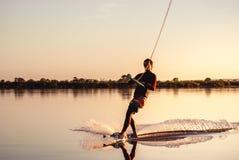 Wakeboarding Silhouette d'athlète avec l'éclaboussure de l'eau image libre de droits