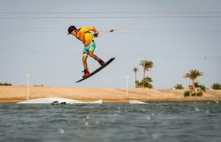 Wakeboarding sportsman jumping air trick move in the cablepark, active sports and life style stock photography