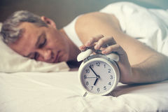 Waked Up. Hand turns off the alarm clock waking up at morning . stock photography