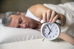 Waked Up. Hand turns off the alarm clock waking up at morning . Royalty Free Stock Image