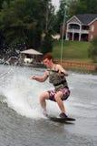 Wakeskating Fun. Teenage boy skating the wake on the lake stock photos