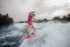 Wakesurfer женщины ехать вниз с голубого брызгая реки против sk стоковые изображения rf