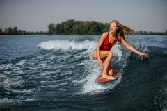 Wakesurfer rubio atractivo de la mujer que monta abajo del splashin azul imagenes de archivo