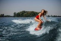 Wakesurfer rubio delgado de la mujer que monta abajo de la onda que salpica azul imagenes de archivo