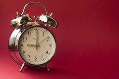 Wakey wakey. Traditional style alarm clock showing 9 o'clock against a red background Royalty Free Stock Image
