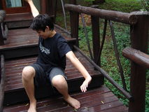 Waking boy on camp steps. A teenage boy stretches as he wakes up from sleeping on steps of camp in woods Stock Photo