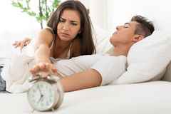 Waking up. Beautiful Young couple sleeping in bed in the morning. Sleepy Girlfriends waking up with alarm clock Royalty Free Stock Photography