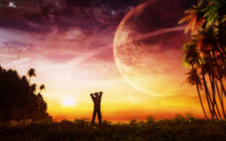 Waking Up In Paradise. A man woke up in paradise and watching the amazing celestial poetry. Natural environment with flock of birds, ringed planets, setting sun stock illustration