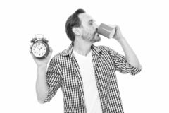Waking up refreshed and energized. Bearded mature man drinking coffee with clock in hand. Mature man with alarm clock. Drinking hot drink. Its time to drink stock images