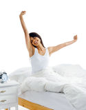 Waking up woman. Tired sleepy woman waking up and yawning with a stretch while sitting in bed isolated on white background Stock Images