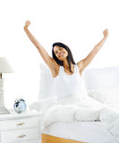 Waking up woman. Tired sleepy woman waking up and yawning with a stretch while sitting in bed isolated on white background Stock Photography