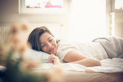 Waking up. Woman in bed. Young woman waking up in bed. Space for copy stock images