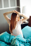 Waking up. Young woman waking up and stretching in her bed stock image