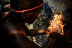 Walarano-Dorf, Malekula-Insel/Vanuatu - 9. JULI 2016: lokaler Stammes- Mann, der zu einem Feuer durchbrennt, um es auf dem tradit lizenzfreie stockfotos
