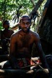 Walarano by, Malekula ö/Vanuatu - 9 JULI 2016: lokal stam- man som trummar i en fjäderhuvudbonad under en by arkivfoto