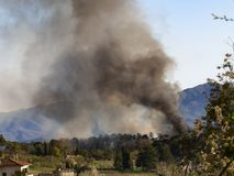 Wald auf Feuer, Italien Raucht Wogen über brennenden Bäumen Nahe Fornoli-Dorf Lunigiana, im März 2019 Vertikales Bild stockbilder