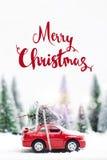 Wald des verschneiten Winters mit dem roten Miniaturauto, das ein Weihnachten transportiert Stockbild