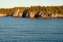 Wald und Klippen mit Höhlen an Lakeshore Lizenzfreie Stockbilder