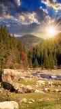 Waldfluß mit Steinen und Moos bei Sonnenuntergang Lizenzfreies Stockfoto