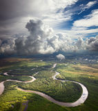 Waldfluß unter den weißen Wolken Stockfotografie