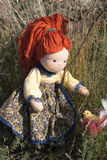 Waldorf doll and bird. Waldorf doll playing with a bird at the nature royalty free stock image