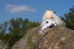 Waldorf doll at the nature. Sky and rock royalty free stock images