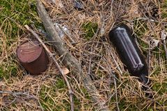 Waldverschmutzung mit Abfallplastikflaschen, Glasflaschen, Metallrostdosen stockfotografie