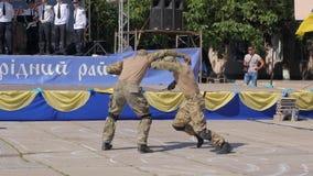 Waleczni sporty żołnierze w wojskowego uniform angażują w walce z broniami w ich rękach na ulicie zbiory