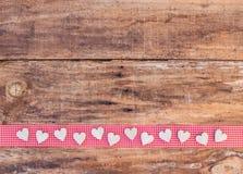 Walentynek serc dekoracja na czerwonym faborku rabatowym i nieociosanym drewnianym tle Zdjęcia Stock