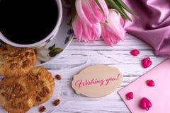 Walentynka dnia kartka z pozdrowieniami z różowymi tulipanu coffe filiżanki ciastkami i literowanie życzy ciebie obrazy stock