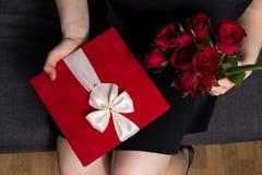 Walentynka dnia niespodzianka - kobiety mienie w ręka czerwonym prezencie i różanym bukiecie zdjęcie royalty free