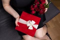 Walentynka dnia niespodzianka - kobiety mienie w ręka czerwonym prezencie i różanym bukiecie zdjęcie stock