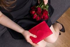 Walentynka dnia niespodzianka, piękna kobieta trzyma czerwone róże i czerwoną kopertową wiadomość obraz stock
