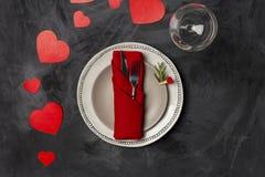 Walentynka dnia porcji talerz z rozwidleniem, nożem i czerwieni sercami, kształtował przy czarnym tłem zdjęcia royalty free
